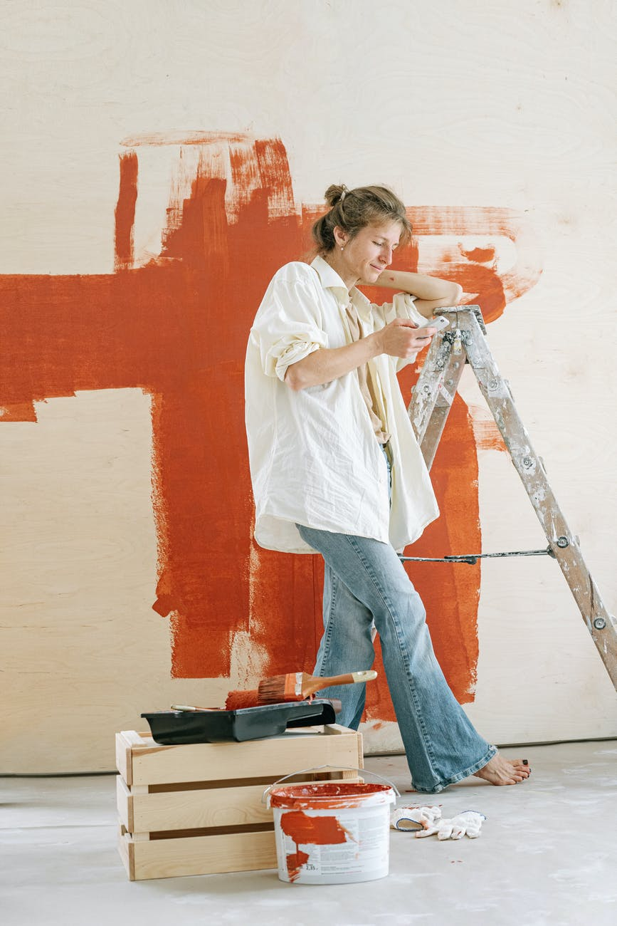 woman in white shirt and blue denim jeans standing beside red wall